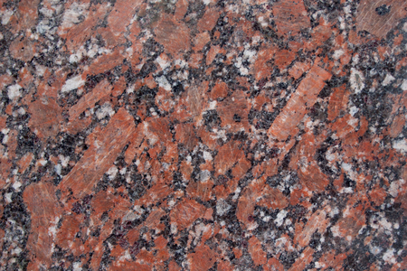 Reddish-brown granite texture with black and gray spots. Used as a background. Copy space for your text.