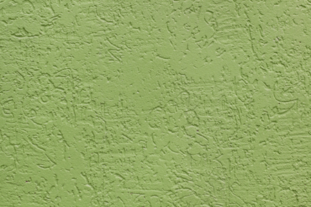 Green flat rough painted wall with many cavities. Used as a background. Copy space for your text.