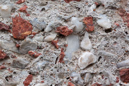 Concrete wall with lining from bits of broken brick. Used as a background. Copy space for your text.