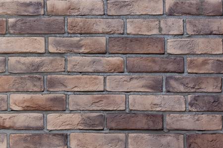 Brick wall with variegated brown bricks. Used as a background. Copy space for your text. Stock Photo