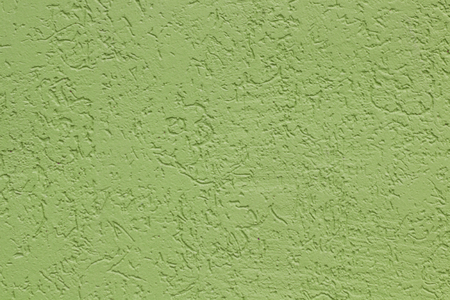 Green flat rough painted cement wall with many cavities. Seamless texture. Used as a background. Copy space for your text.