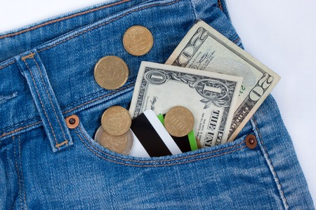 Wallet, credit cards and ready money are lying in side pocket of blue jeans. Modern lifestyle.