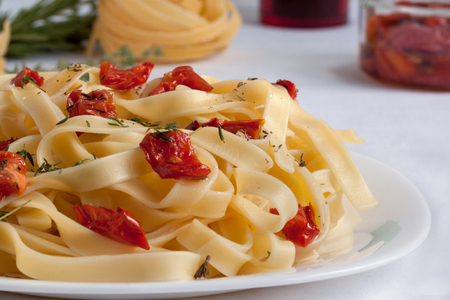 Fettuccine pasta with sun-dried tomatoes and fresh herbs. Close up. Healthy lifestyle.