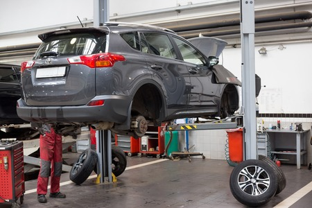 Russia, Izhevsk - April 21, 2018: Automobile workshop. Replacement and wheel alignment on a hydraulic lift. Modern service. 新聞圖片
