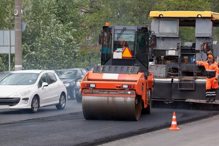 Russia, Izhevsk - May 30, 2018: Road work. Repair and replacement of old asphalt pavement. Asphalt layover. Using a special road roller. Editorial