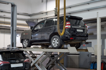 Russia, Izhevsk - October 20, 2018: Automobile workshop. Car standing on the hydraulic lift for repair. 新聞圖片