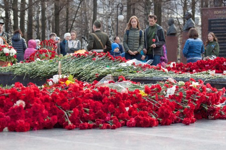 Russia, Izhevsk - May 9, 2018: The people are laying flowers at the memorial to the fallen soldiers of World War II. Red carnation flowers on a memorial marble board. Victory in Europe Day.