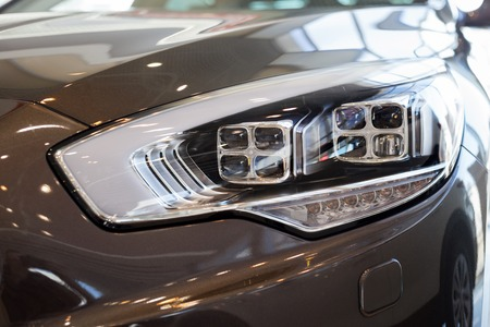 New modern car with elegant quadrate head lamps. Front view. Close up. Imagens