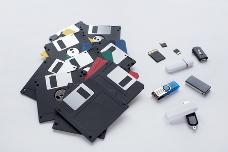 The evolution of digital data storage device. Floppy disks, flash drives and memory cards isolated on a white background. Modern and retro technology. 版權商用圖片