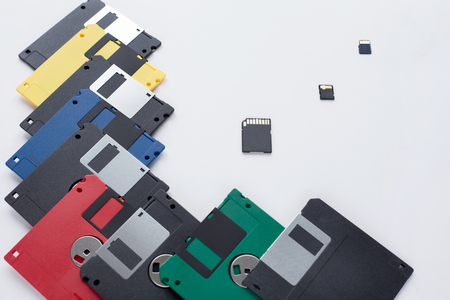 The evolution of digital data storage device. Floppy disks vs small memory cards. Isolated on a white background.