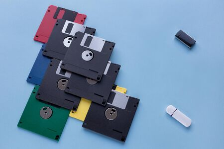 The evolution of digital data storage device. Floppy disks vs small flash drives. Isolated on a blue background. Modern and retro technology. 免版税图像