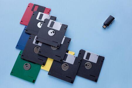 Die Evolution des digitalen Datenspeichers. Disketten im Vergleich zu kleinen Flash-Laufwerken. Auf blauem Hintergrund isoliert. Moderne und Retro-Technologie.