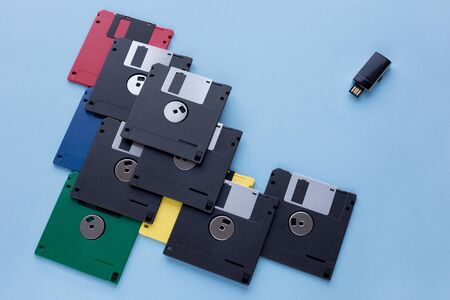 The evolution of digital data storage device. Floppy disks vs small flash drive. Isolated on a blue background. Modern and retro technology.