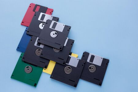 Multi-colored flexible disks isolated on a blue background. Copy space for your text. Retro style. 版權商用圖片