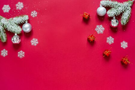 Snowy sprigs of pine, snowflakes, chrismas balls and christmas gifts isolated on red background.