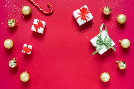 Golden chrismas balls, christmas gifts and caramel cane isolated on red background. Concept of Christmas and new year.