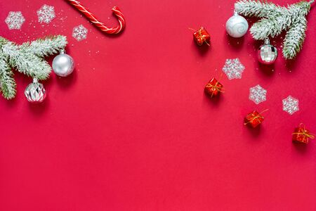 Snowy sprigs of pine, snowflakes, chrismas balls, christmas gifts and caramel cane isolated on red background. Concept of Christmas and new year.