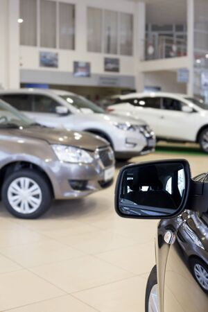 New cars at dealer showroom. Themed blur background with bokeh effect. For use as a background. 스톡 콘텐츠