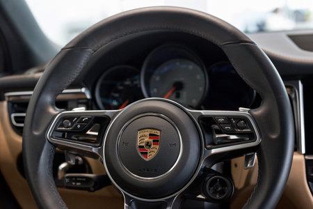 Russia, Izhevsk - August 04, 2020: Porsche showroom. Steering wheel and dashboard of new Macan S car. Volkswagen Auto Group. Prestigious vehicles.