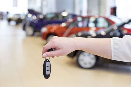 Dealer woman holding keys to a new car. Modern and prestigious vehicles. For use as a background.