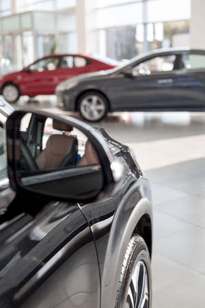 New modern cars on the blur background. Car auto dealership. Prestigious vehicles.