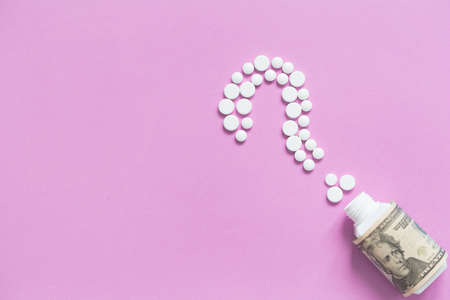 Medical bootle with dollars, sign of question from white pills. The concept of insurance medicine, high cost of drugs. Isolated on a pink background. Copy space.