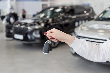 Saleswoman holding keys to a new car. Car auto dealership. Modern and prestigious vehicles.