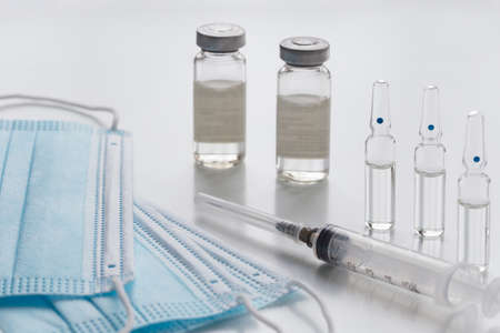 Protective face masks, medical bottles, ampullas and expendable syringe for vaccination. Coronavirus vaccination concept. COVID-19 outbreak - Wuhan, China. Standard-Bild