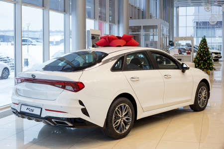 Russia, Izhevsk - December 28, 2020: KIA showroom. New K5 business class car in dealer showroom. Back and side view. Famous world brand.