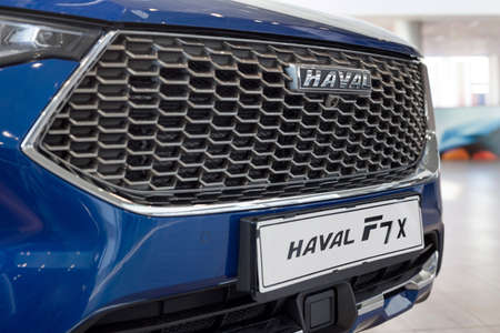 Russia, Izhevsk - February 17, 2021: Haval logo on a bumper of new car F7X at dealership showroom. Car manufacturer from China. Modern transportation.