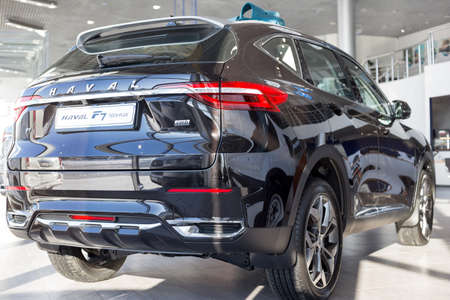 Russia, Izhevsk - February 17, 2021: Haval showroom. New modern F7 Tech Plus car in dealer showroom. Back and side view. Car manufacturer from China.