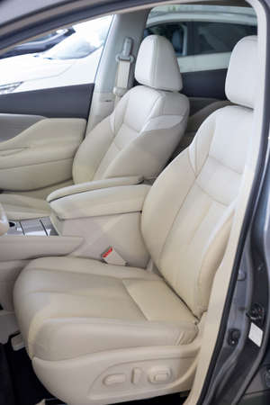 Russia, Izhevsk - February 19, 2021: Nissan showroom. Interior of new modern Murano car. Driver and passenger seat made from light leather inside car. Famous world brand.