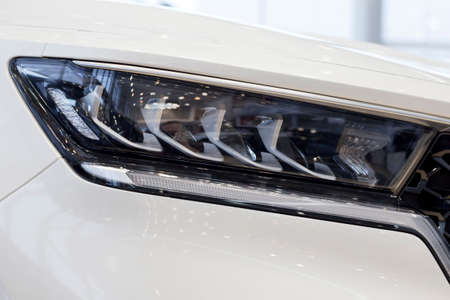 New modern unknown car with elegant head lamps. Cropped image. Close up. Modern transportation. Banque d'images