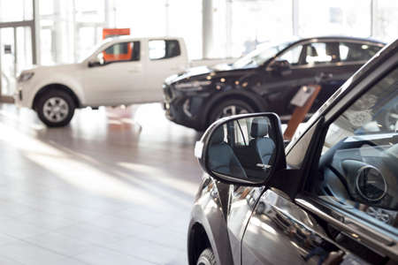 New modern unknown cars at dealer showroom. Car auto dealership. Prestigious vehicles. Themed blur background.