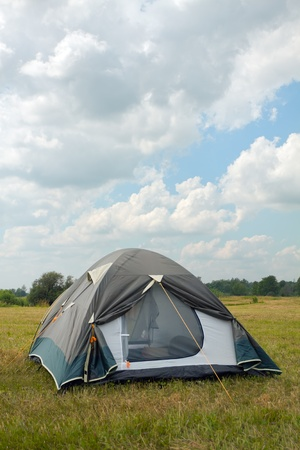 campground: tent on a grass under white clouds Stock Photo