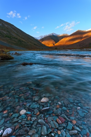 The mountain river with stones in the foreground flowing between glaciers  photo