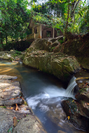 the river with falls and the ancient house in the jungle of Thailand. photo