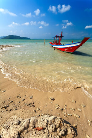 The red wooden boat on the sandy seashore. photo