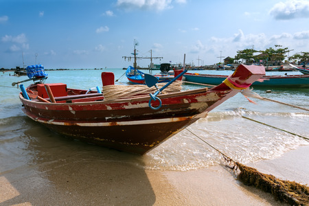 red wooden boat on the sea photo