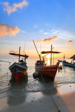 river boat: Boats in the warm glow of sunset on Fishermans beach