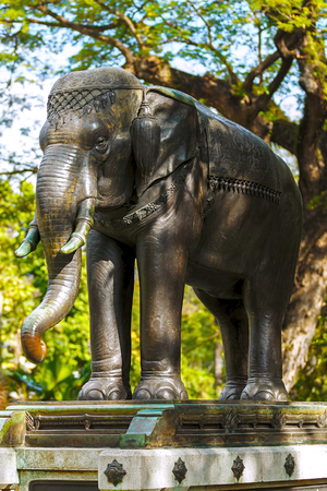 metal sculpture: Metal sculpture of an elephant standing in the park under the trees. Stock Photo