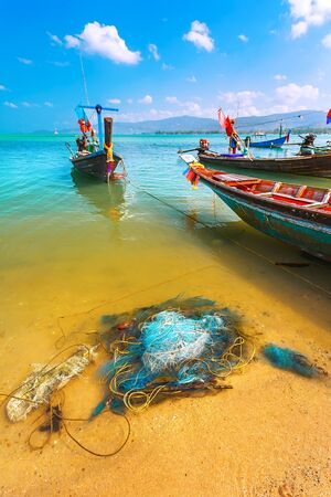 Colored fishing boats in the sea in the turquoise waters. And colourful tackle and nets on the sand Stock Photo