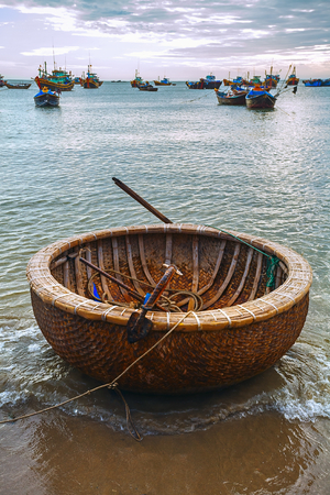paddles: National round wicker boat on the beach. Sea sunset and the fishing boats.