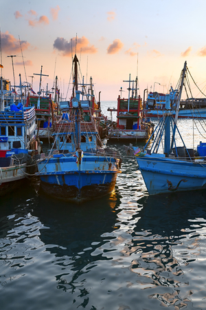 Landscape sea port of Thailand at sunset with ships reflecting in the water. Stock Photo