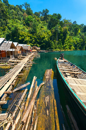 Floating house on a lake in the jungle with a wooden bridge and the national boat. Thailand.
