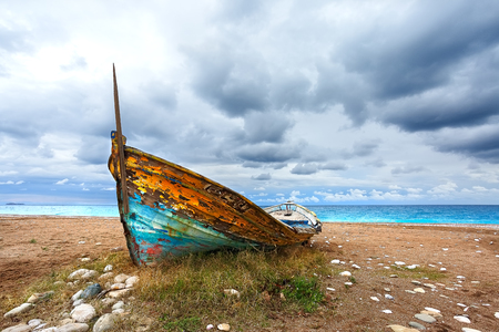 Old wooden boat on the sandy shore of the beach. Sunset on the beach. Sparse vegetation.