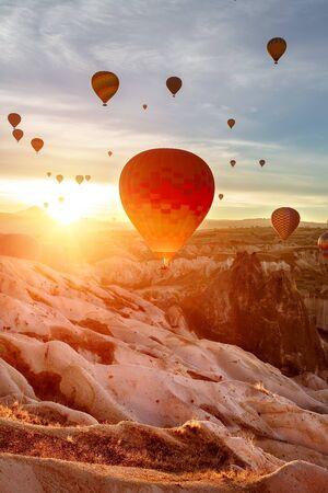 Colored balloons rise into the sky. Sunrise. The sun's rays Shine into the camera lens. Turkey, Cappadocia. Foto de archivo