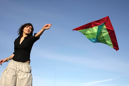 flying a kite: the brunette starts the snake, on a background of the blue sky