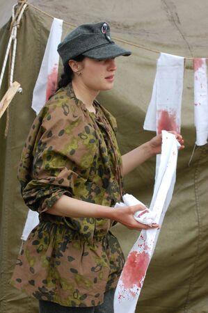 KIEV, UKRAINE - MAY 10,2010 : member of Red Star history club wears historical military German paramedic uniform during historical reenactment of 1945 WWII, May 10, 2010 in Kiev, Ukraine  Stock Photo - 7537145