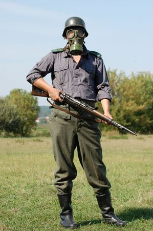 vintage military rifle: German soldier in gas mask. WW2 reenacting  Stock Photo